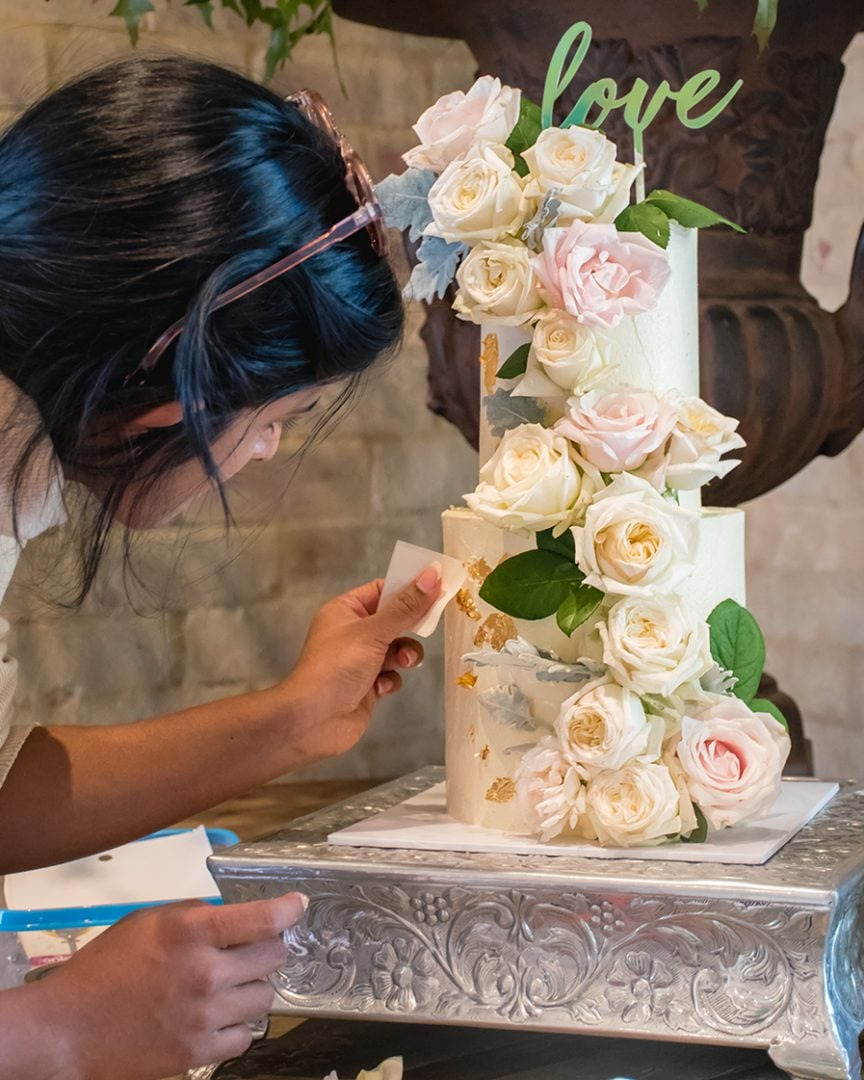 Image of Ruwi decorating a wedding cake at a venue