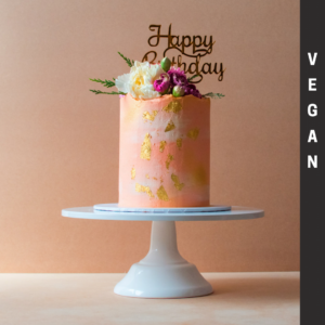 Pink vegan cake with gold flakes and flowers