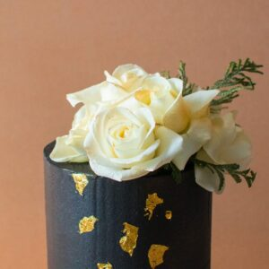 Close up of a black icing cake with gold flakes and white flowers