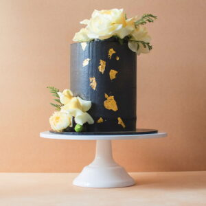 Large black icing cake with gold flakes and white flowers