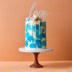 Large cake with blue shade icing and white chocolate drip