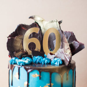 Close up of 60 birthday sign and chocolate shards on top of cake