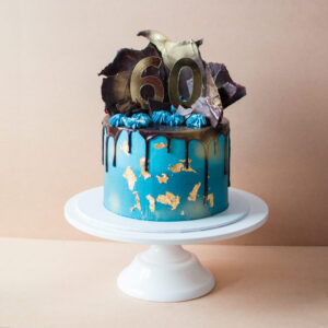 Blue icing cake with chocolate drip and chocolate shards on top