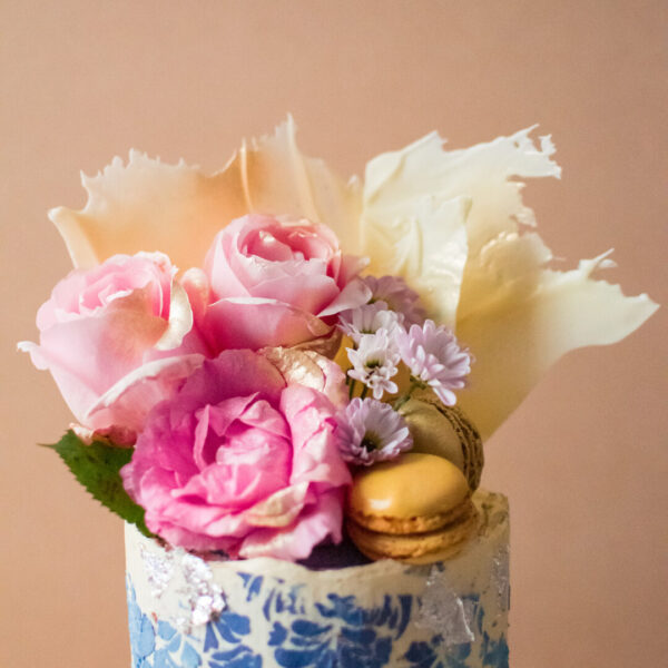 Close up of flowers and macarons and white chocolate shards on top of cake