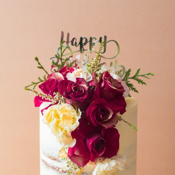 Close up of a semi-naked cake with red roses and happy birthday cake topper