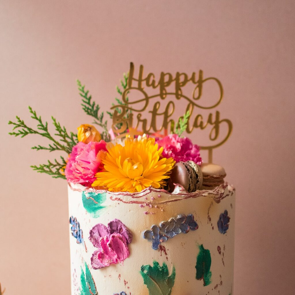 Close up of cake with buttercream flowers and macaroons