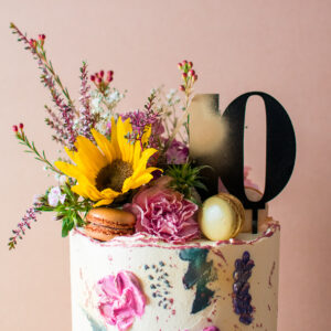 close up of a buttercream cake and macaroons, sunflowers and a topper