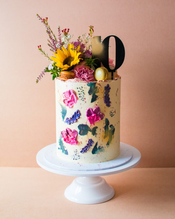 White buttercream cake with buttercream flowers and sunflower on top