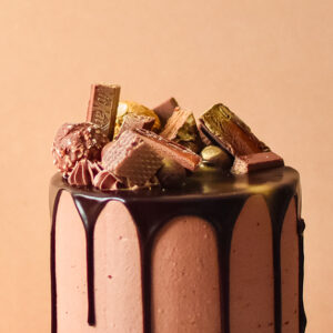 a close up image of an chocolate cake with various chocolates on top