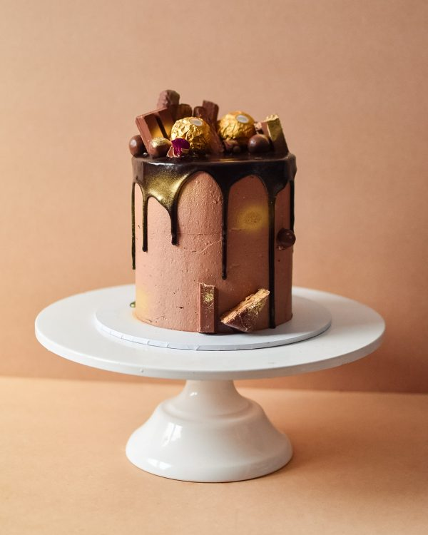 a chocolate cake with chocolate drip and chocolates decorated on top