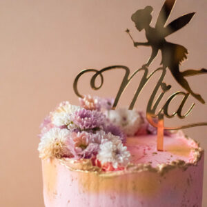 Close up of a fairy cake topper and flowers
