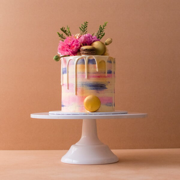 Macaroon and white chocolate drip cake with flowers