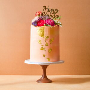 Large pink cake with gold flakes and flowers