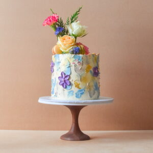 Cake with pastel icing flowers and real flowers for a birthday