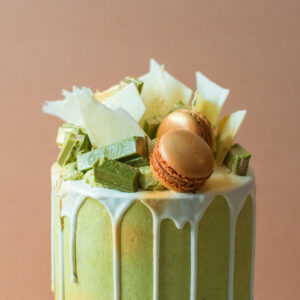 Close up of a matcha cake with white chocolate drip and macarons and green tea kitkats