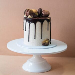 a chocolate cake with chocolate drip and macaroons on top