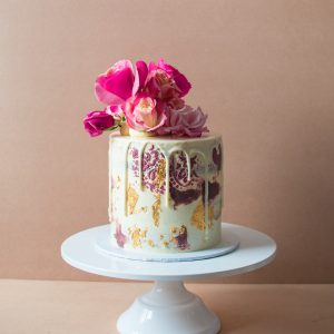 a mini cake with vintage design on the sides and chocolate drip and flowers on top