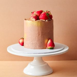 Chocolate and strawberry cake with gold spray painted on the sides