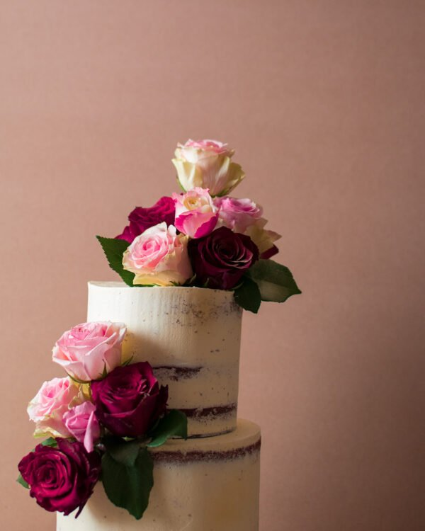 Close up of semi-naked wedding cake with roses