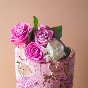 Close up of a pink cake with pink roses on top