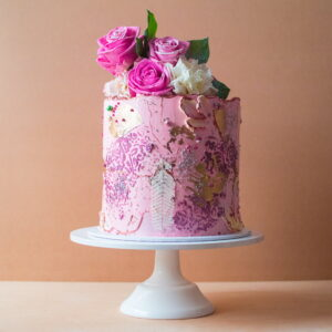 Large pink cake with vintage pattern on the sides and pink roses on top