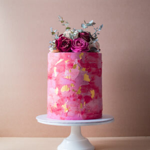 Red and pink buttercream cake with gold flakes and flowers on top