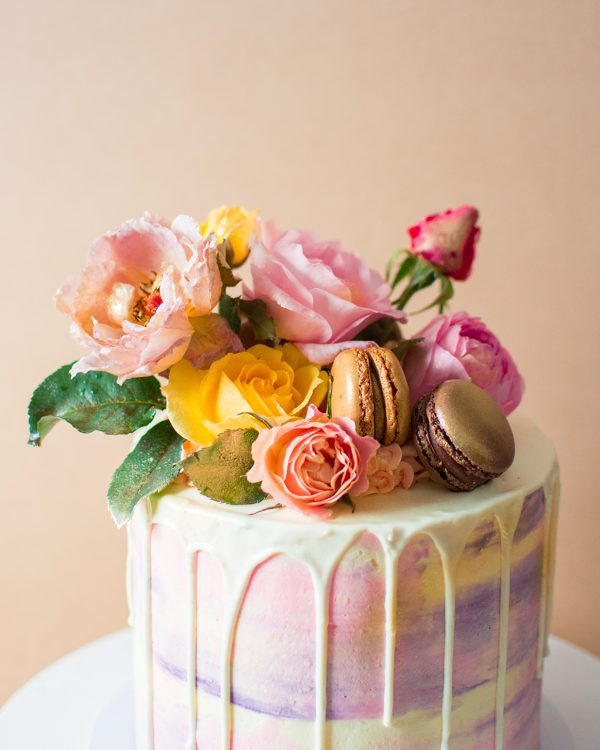 A close up image of a pink and purple fairy birthay cake with flowers and chocolate macaroons