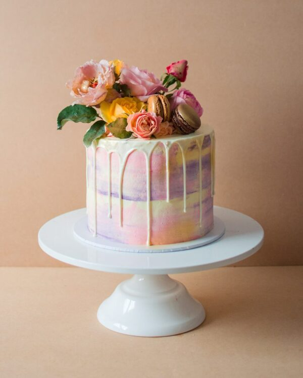 A small watercolour fairy birthday cake with pink and purple design and flowers on top