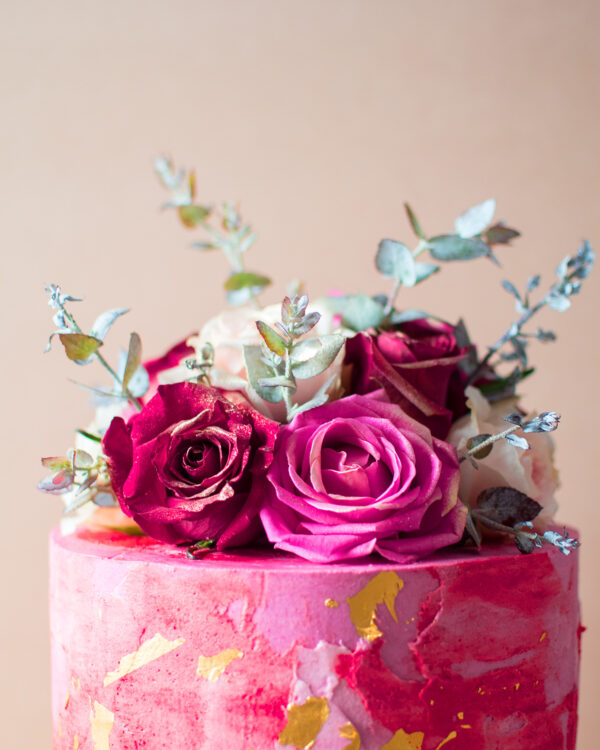 Close up of a pink cake with gold flakes and vintage flowers