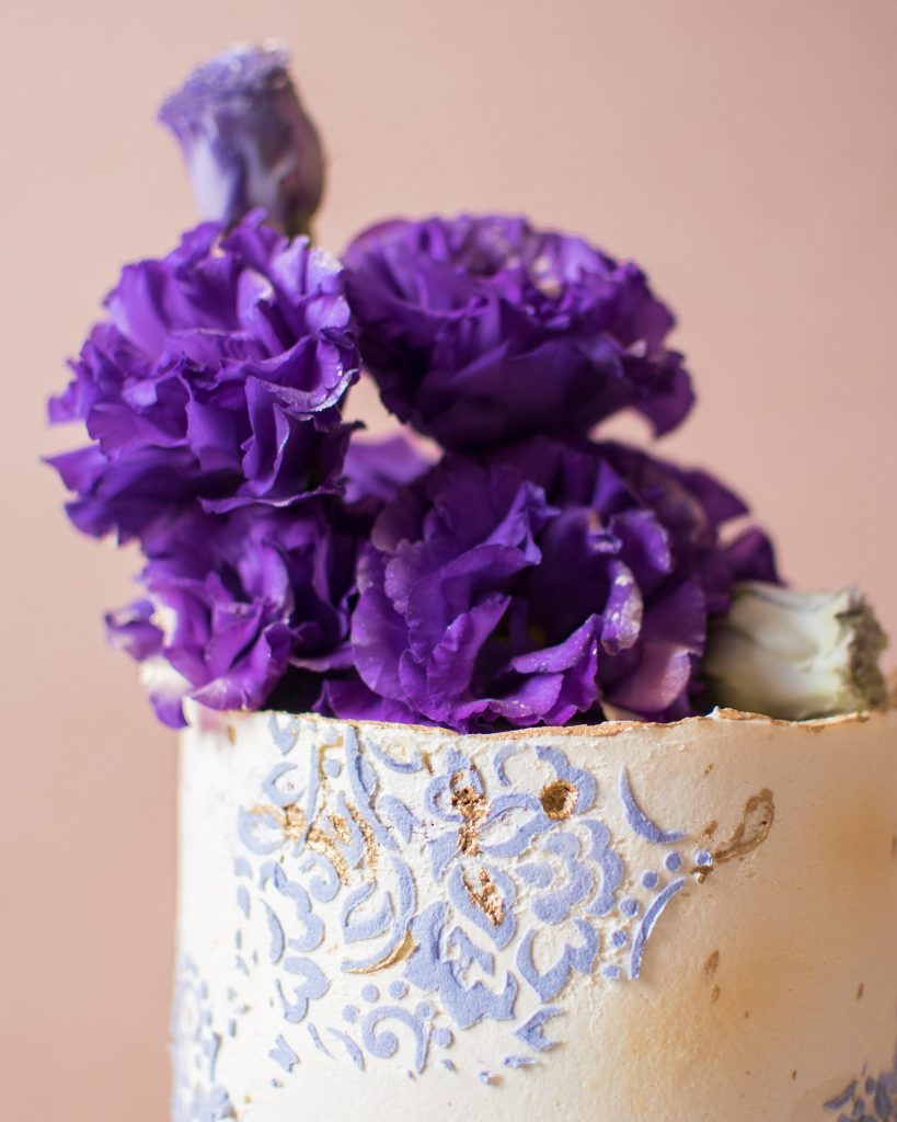 White frosted cake with purple flowers
