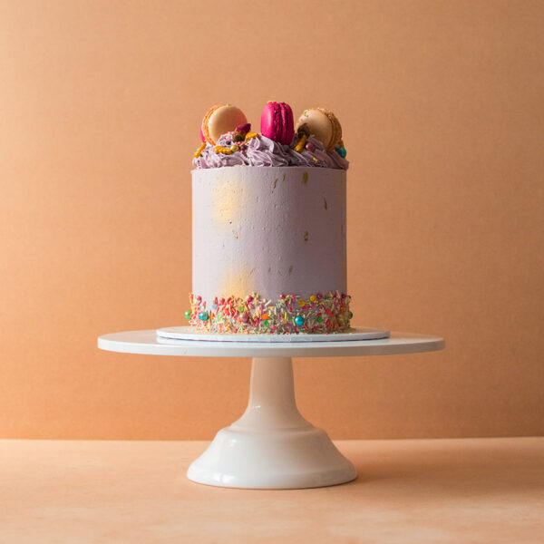 Purple cake with macaroons and sprinkles on the sides and top
