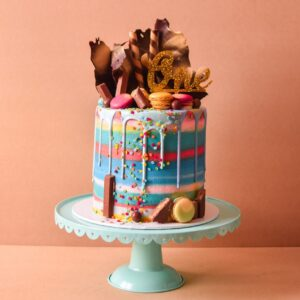 a rainbow cake with multiple colours sand chocolates and drip on top