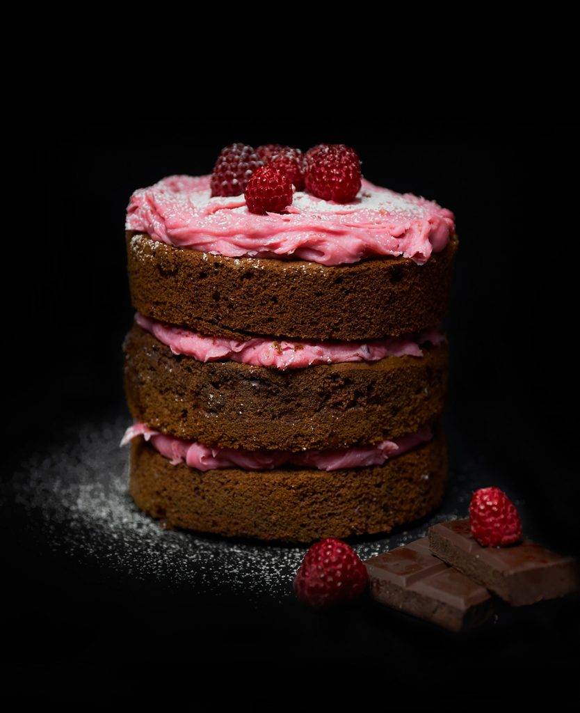 Dark chocolate and raspberry mini cake with raspberry frosting on top with icing sugar