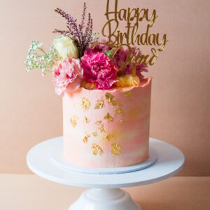 Pink flower cake with gold flakes and happy birthday topper