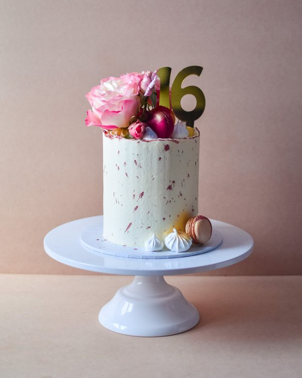 a rose gold 16th birthday cake with rustic look and flower on top