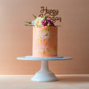 Light pink cake with flowers and a happy birthday topper