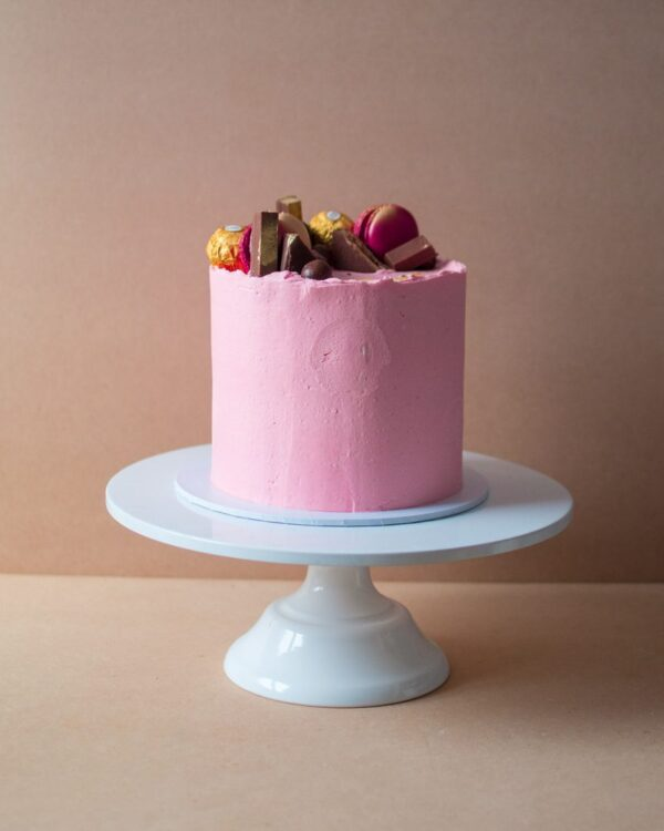 a pink cake for kids with chocolates on top