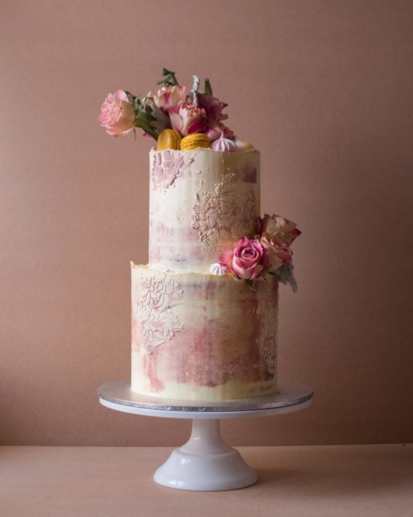 Two tier faded pink cake with pink and red flowers with macaroons