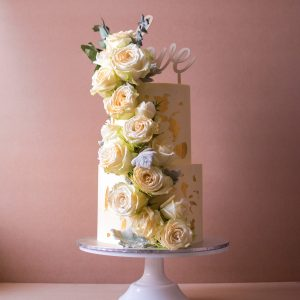 Two tier White wedding cake with white flowers and gold flakes