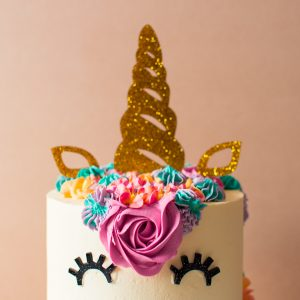 a close up image of an unicorn cake with colourful icing for a birthday
