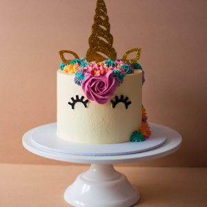 a small unicorn cake with colourful icing on top