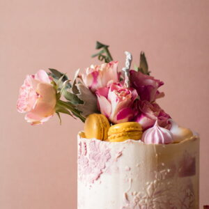 Faded pink pastel single tier cake with pink roses and macaroons