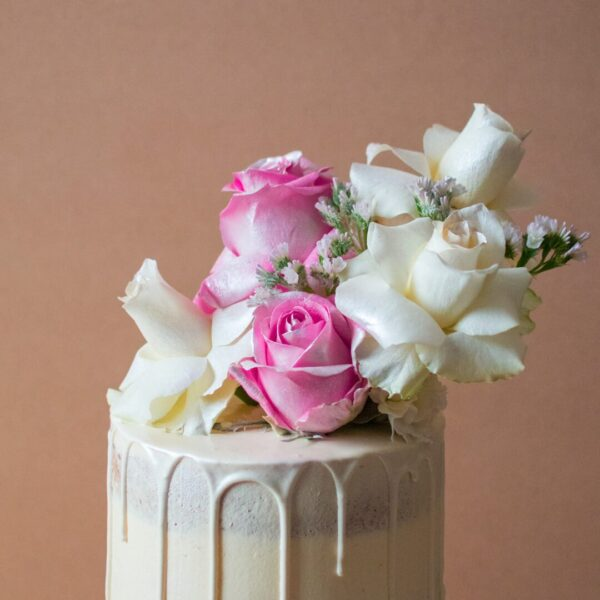 Close up of a white chocolate drip wedding cake with white and rose flowers