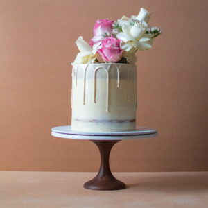 Semi-naked white chocolate drip cake with flowers on top