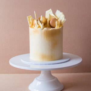 a vanilla cake with white macaroons and white chocolate shards on top